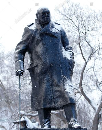 A statue of former British Prime Minister Winston Churchill is covered with a light coating of snow in London, . Heavy snow in parts of Britain is causing disruption to road, rail and air travel and has led to hundreds of schools being closed across the country
