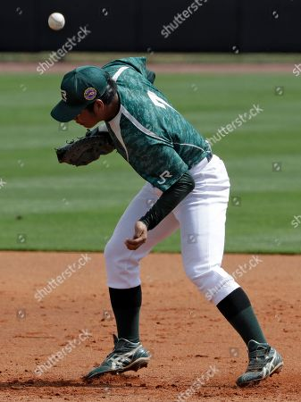 JR East first baseman Maruko boots a ground ball by Major League Baseball free agent Luke Scott during an exhibition baseball game, in Bradenton, Fla. Maruko was able to still get Scott out at first base