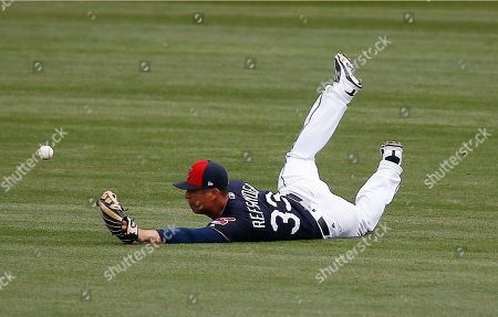 Stock Image of Cleveland Indians right fielder Rob Refsnyder dives in vain for a single hit by Oakland Athletics' Nick Noonan during the fifth inning of a spring training baseball game, in Goodyear, Ariz