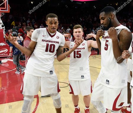 Stock Photo of Daniel Gafford, Jonathan Holmes, Arlando Cook. Arkansas players Daniel Gafford (10) Jonathan Holmes (15) and Arlando Cook celebrate after Arkansas defeated Auburn 91-82 during an NCAA college basketball game, in Fayetteville, Ark