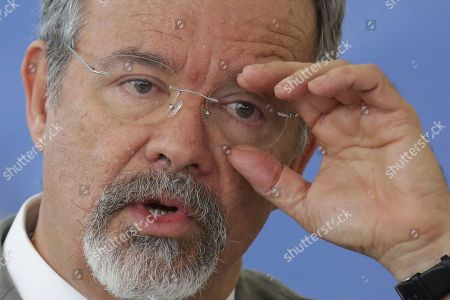 """Brazil's Defense Minister Raul Jungmann adjusts his eyeglasses during a ceremony at the Planalto Presidential Palace to inaugurate the newly created Public Security Ministry, part of President Michel Temer's efforts to combat high crime rates, in Brasilia, Brazil, . Appointed to lead the ministry, Jungmann said the government was analyzing the use of """"collective"""" search warrants, a legal tool that allows for searches of whole streets or even neighborhoods, rather than a single address"""
