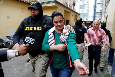 Former first lady of Honduras Rosa Elena Bonilla is escorted by police to a police station in Tegucigalpa, Honduras, . Military police searched the home of the former first couple on Wednesday and arrested Bonilla as part of a corruption probe by an international team of investigators. Authorities did not say if her husband, former President Porfirio Lobo, himself was present