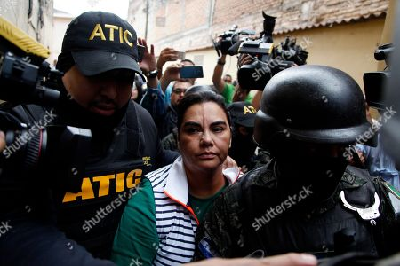 Former first lady of Honduras Rosa Elena Bonilla is escorted by police away from a police station, surrounded by the press in Tegucigalpa, Honduras, . Military police searched the home of the former first couple on Wednesday and arrested Bonilla as part of a corruption probe by an international team of investigators. Authorities did not say if her husband, former President Porfirio Lobo, himself was present
