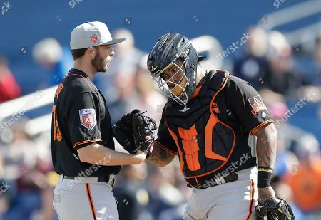Hector Sanchez, Andrew Suarez. San Francisco Giants pitcher Andrew Suarez, left, talks with catcher Hector Sanchez during the a spring training baseball game against the Milwaukee Brewers, in Maryvale, Ariz