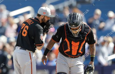 Hector Sanchez, Andrew Suarez. San Francisco Giants pitcher Andrew Suarez (76) talks with catcher Hector Sanchez during the a spring training baseball game against the Milwaukee Brewers, in Maryvale, Ariz