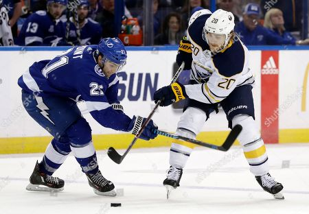 Stock Photo of Brayden Point, Scott Wilson. Buffalo Sabres center Scott Wilson (20) shoots the puck past Tampa Bay Lightning center Brayden Point (21) during the third period of an NHL hockey game, in Tampa, Fla