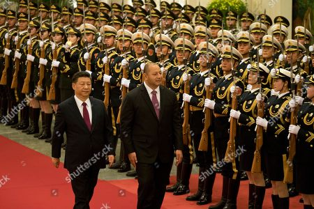 King Tupou VI of Tonga, center walks with Chinese President Xi Jinping during a welcome ceremony held at the Great Hall of the People in Beijing