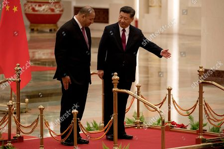 King Tupou VI of Tonga, at left is shown the way by Chinese President Xi Jinping, center during a welcome ceremony held at the Great Hall of the People in Beijing