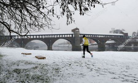 A man runs next the Ponte Coperto (Covered bridge), also known as Ponte Vecchio (Old Bridge), a brick and stone arch bridge over the Ticino River, during a snowfall in Pavia, some 40 kilometers (24 miles) south east of Milan, Italy, . Persistent snow and freezing conditions from a Siberian cold snap are causing delays in many parts of mainland Europe, with roads and train services hit particularly hard
