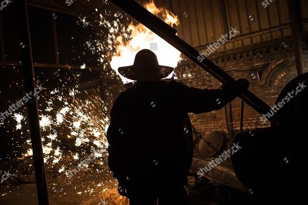 A member of Wang De's Chinese traditional molten iron performance team prepares for the performance of throwing molten iron against a cold stone city wall to create sparks like fireworks, commonly known as 'Da Shu Hua' in Nuanquan Town, rural Zhangjiakou city in Hebei province, China, 28 February 2018 (issued 01 March 2018). Wang De's Chinese traditional molten iron performance team is artists in Nuanquan Town still practicing 'Da Shu Hua', the art of throwing molten iron to create fireworks. When the iron is melted down it has a temperature of 1600 degrees Celsius. The traditional act has become popular in recent years and thousands of people descend on the town to watch their performance every day during the Spring Festival period.