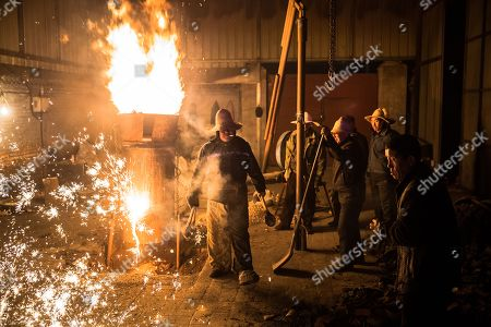 Members of Wang De's Chinese traditional molten iron performance team prepare for the performance of throwing molten iron against a cold stone city wall to create sparks like fireworks, commonly known as 'Da Shu Hua' in Nuanquan Town, rural Zhangjiakou city in Hebei province, China, 28 February 2018 (issued 01 March 2018). Wang De's Chinese traditional molten iron performance team is artists in Nuanquan Town still practicing 'Da Shu Hua', the art of throwing molten iron to create fireworks. When the iron is melted down it has a temperature of 1600 degrees Celsius. The traditional act has become popular in recent years and thousands of people descend on the town to watch their performance every day during the Spring Festival period.