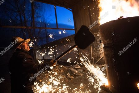 A member of Wang De's Chinese traditional molten iron performance team shovels scrap metal into a furnace to be melted for the performance of throwing molten iron against a cold stone city wall to create sparks like fireworks, commonly known as 'Da Shu Hua' in Nuanquan Town, rural Zhangjiakou city in Hebei province, China, 28 February 2018 (issued 01 March 2018). Wang De's Chinese traditional molten iron performance team is artists in Nuanquan Town still practicing 'Da Shu Hua', the art of throwing molten iron to create fireworks. When the iron is melted down it has a temperature of 1600 degrees Celsius. The traditional act has become popular in recent years and thousands of people descend on the town to watch their performance every day during the Spring Festival period.