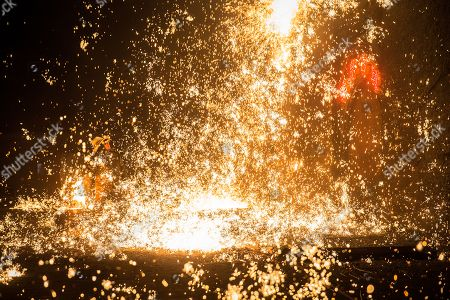 A member of Wang De's Chinese traditional molten iron performance team throws molten iron against a cold stone city wall to create sparks like fireworks, commonly known as 'Da Shu Hua' in Nuanquan Town, rural Zhangjiakou city in Hebei province, China, 28 February 2018 (issued 01 March 2018). Wang De's Chinese traditional molten iron performance team is artists in Nuanquan Town still practicing 'Da Shu Hua', the art of throwing molten iron to create fireworks. When the iron is melted down it has a temperature of 1600 degrees Celsius. The traditional act has become popular in recent years and thousands of people descend on the town to watch their performance every day during the Spring Festival period.