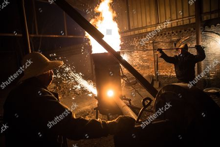 Members of Wang De's Chinese traditional molten iron performance team shovel scrap metal into a furnace to be melted for the performance of throwing molten iron against a cold stone city wall to create sparks like fireworks, commonly known as 'Da Shu Hua' in Nuanquan Town, rural Zhangjiakou city in Hebei province, China, 28 February 2018 (issued 01 March 2018). Wang De's Chinese traditional molten iron performance team is artists in Nuanquan Town still practicing 'Da Shu Hua', the art of throwing molten iron to create fireworks. When the iron is melted down it has a temperature of 1600 degrees Celsius. The traditional act has become popular in recent years and thousands of people descend on the town to watch their performance every day during the Spring Festival period.
