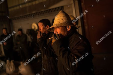 Members of Wang De's Chinese traditional molten iron performance team wait as they prepare for the performance of throwing molten iron against a cold stone city wall to create sparks like fireworks, commonly known as 'Da Shu Hua' in Nuanquan Town, rural Zhangjiakou city in Hebei province, China, 28 February 2018 (issued 01 March 2018). Wang De's Chinese traditional molten iron performance team is artists in Nuanquan Town still practicing 'Da Shu Hua', the art of throwing molten iron to create fireworks. When the iron is melted down it has a temperature of 1600 degrees Celsius. The traditional act has become popular in recent years and thousands of people descend on the town to watch their performance every day during the Spring Festival period.