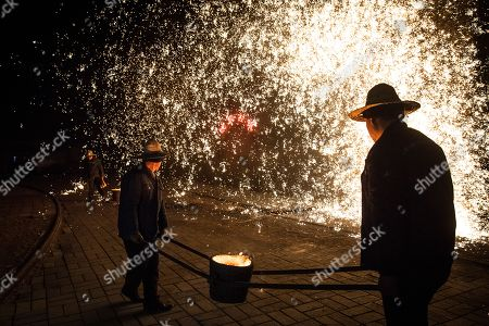 Members of Wang De's Chinese traditional molten iron performance team carry molten iron for the performance of throwing molten iron against a cold stone city wall to create sparks like fireworks, commonly known as 'Da Shu Hua' in Nuanquan Town, rural Zhangjiakou city in Hebei province, China, 28 February 2018 (issued 01 March 2018). Wang De's Chinese traditional molten iron performance team is artists in Nuanquan Town still practicing 'Da Shu Hua', the art of throwing molten iron to create fireworks. When the iron is melted down it has a temperature of 1600 degrees Celsius. The traditional act has become popular in recent years and thousands of people descend on the town to watch their performance every day during the Spring Festival period.