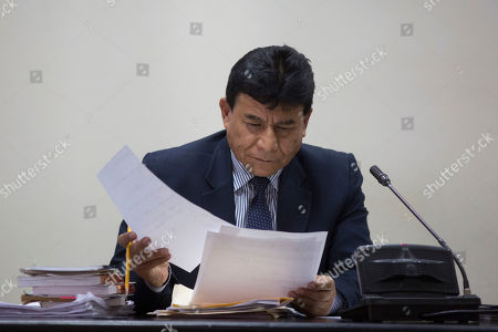 Judge Jose Eduardo Cojulum looks over documents in his courtroom in Guatemala City, . Cojulum is to decide whether a case of suspected corruption proceeds against former President Alvaro Colom and 12 former Cabinet ministers, including Colom's finance minister, Juan Alberto Fuentes, who recently resigned as the president of Oxfam International