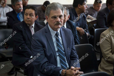Juan Alberto Fuentes, former Guatemalan finance minister, waits handcuffed in a courtroom for the for the ruling on whether he will be released, in Guatemala City, . A judge is to decide whether a case of suspected corruption proceeds against former President Alvaro Colom and 12 former Cabinet ministers, that include Fuentes who recently resigned as the president of Oxfam International