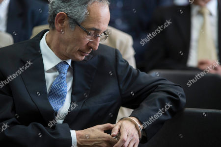 Former Guatemalan President Alvaro Colom touches the chain of the handcuff on his left wrist, as he waits to hear the court ruling on whether he will be released, in Guatemala City, . Colom defended his actions Wednesday in a case of suspected corruption involving bus concessions, saying his order for a $35 million upgrade to the public transit system was legitimate