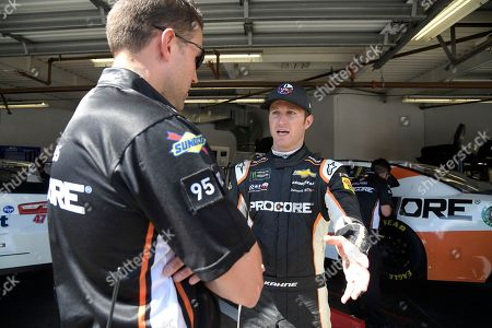 Driver Kasey Kahne, right, talks to a crew member in the garage during practice for the NASCAR Daytona 500 auto race at Daytona International Speedway, in Daytona Beach, Fla