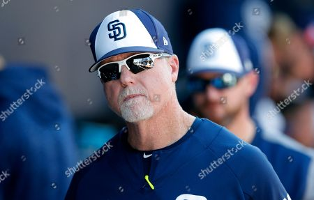 San Diego Padres bench coach Mark McGwire walks in the dugout during the fifth inning of a spring training baseball game against the Kansas City Royals, in Peoria, Ariz
