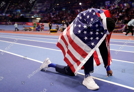 United States' Will Claye kneels on the track after winning the gold medal in the men's triple jump final at the World Athletics Indoor Championships in Birmingham, Britain