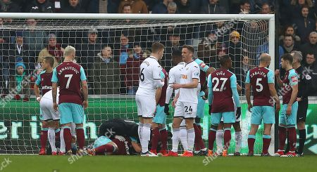 Stock Image of Winston Reid of West Ham United receives treatment for a knee injury after landing awkwardly