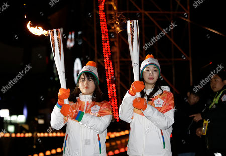Yuna Kim, Bong Hyeon-chae. South Korean Olympic figure skating champion Yuna Kim, right, and para-cross country skier Bong Hyeon-chae carry torches after the Paralympic Flame Unifying Ceremony at Olympic Park in Seoul, South Korea, . The Pyeongchang 2018 Paralympic Winter Games is held from March 9-18