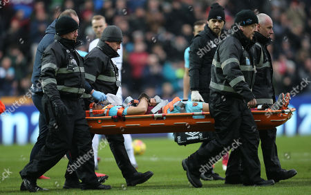 Winston Reid of West Ham United is stretchered from the pitch