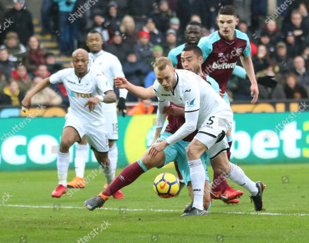 Mike van der Hoorn of Swansea City and Winston Reid of West Ham United clash as they look to win the ball
