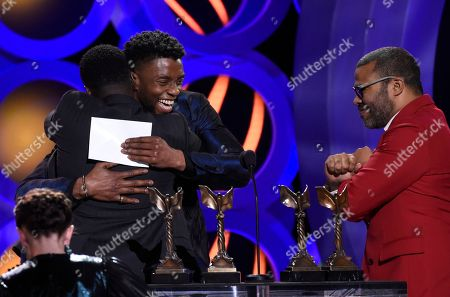 """Chadwick Boseman, Daniel Kaluuya, Jordan Peele. Chadwick Boseman, left, embraces Daniel Kaluuya while Jordan Peele, from right, comes on stage as """"Get Out"""" wins the award for best feature at the 33rd Film Independent Spirit Awards, in Santa Monica, Calif"""