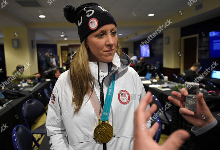 Meghan Duggan, of the gold medal winning US women's Olympic hockey team, listens to a question from the media before an outdoor NHL hockey game between the Washington Capitals and the Toronto Maple Leafs, in Annapolis, Md