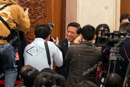 Zhang Yesui, center, a spokesman for the National People's Congress, arrive for a press conference on the eve of the annual legislature opening session at the Great Hall of the People in Beijing