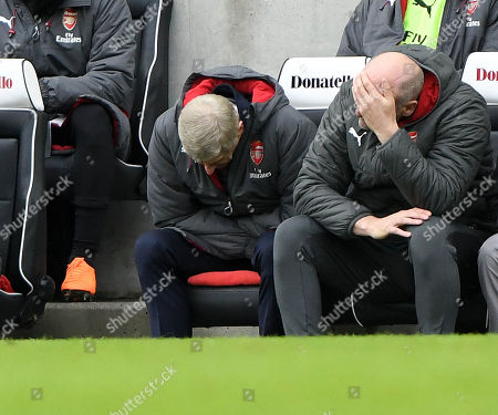 Arsene Wenger Arsenal manager and Steve Bould hang their heads.