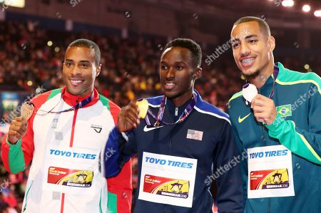 United States' gold medal winner Will Claye is flanked by Portugal's bronze medal winner Nelson Evora, left, and Brazil's silver medal winner Almir Dos Santos after the ceremony for the men's triple jump at the World Athletics Indoor Championships in Birmingham, Britain
