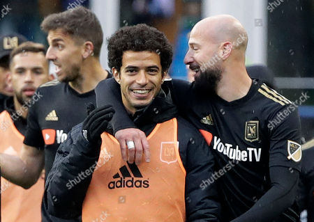 Los Angeles defender Laurent Ciman, right, celebrates with defender Omar Gaber, center, after Los Angeles beat the Seattle Sounders 1-0 in an MLS soccer match, in Seattle