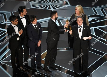 "Darla K. Anderson, Adrian Molina, Anthony Gonzalez, Gael Garcia Bernal, Benjamin Bratt, Lee Unkrich. Lee Unkrich, center, and from back left, Gael Garcia Bernal, Benjamin Bratt, Anthony Gonzalez, Adrian Molina and Darla K. Anderson accept the award for best animated feature film for ""Coco"" at the Oscars, at the Dolby Theatre in Los Angeles"
