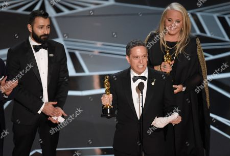 """Stock Image of Adrian Molina, Lee Unkrich, Darla K. Anderson. Adrian Molina, from left, Lee Unkrich, and Darla K. Anderson accept the award for best animated feature film for """"Coco"""" at the Oscars, at the Dolby Theatre in Los Angeles"""