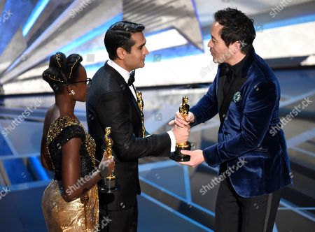 """Stock Image of Lupita Nyong'o, Kumail Nanjiani, Paul Denham Austerberry. Lupita Nyong'o, from left, and Kumail Nanjiani present Paul Denham Austerberry the award for best production design for """"The Shape of Water"""" at the Oscars, at the Dolby Theatre in Los Angeles"""