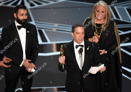"""Adrian Molina, Lee Unkrich, Darla K. Anderson. Adrian Molina, from left, Lee Unkrich, and Darla K. Anderson accept the award for best animated feature film for """"Coco"""" at the Oscars, at the Dolby Theatre in Los Angeles"""