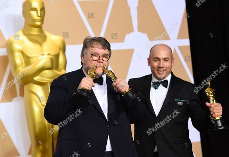 """Guillermo del Toro, J. Miles Dale. Guillermo del Toro, left, winner of the awards for best director for """"The Shape of Water"""" and best picture for """"The Shape of Water"""", and J. Miles Dale, winner of the award for best picture for """"The Shape of Water"""", pose in the press room at the Oscars, at the Dolby Theatre in Los Angeles"""