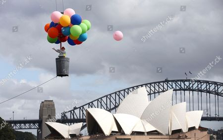 A ballon escapes as Opera Australia artistic director Lyndon Terracini rides in a garbage can under a balloon canopy over Sydney Harbour as he stands in for the character Parpignol during a test run of the prop for Puccini's La Boheme opera in Sydney, . The production of La Boheme is set in a wintery 1960s Parisian landscape and opens on March 23