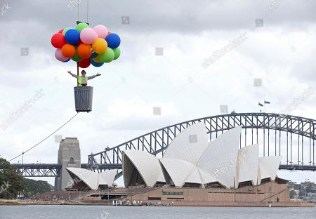 Opera Australia artistic director Lyndon Terracini rides in a garbage can under a balloon canopy over Sydney Harbour as he stands in for the character Parpignol during a test run of the prop for Puccini's La Boheme opera in Sydney, . The production of La Boheme is set in a wintery 1960s Parisian landscape and opens on March 23