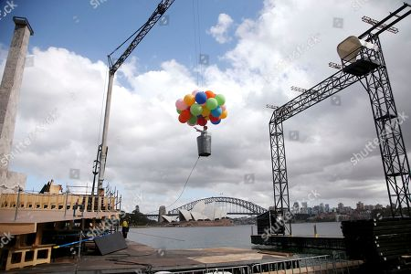 Opera Australia artistic director Lyndon Terracini rides in a garbage can under a balloon canopy over Sydney Harbour and the set construction as he stands in for the character Parpignol during a test run of the prop for Puccini's La Boheme opera in Sydney, . The production of La Boheme is set in a wintery 1960s Parisian landscape and opens on March 23