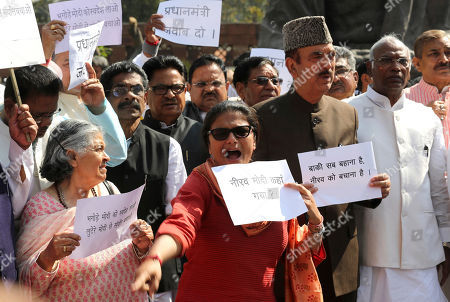 """Indian Congress party lawmakers shout slogans during a protest outside Indian parliament house in New Delhi, India, . The protest was against the ruling Bharatiya Janata Party and billionaire jeweler Nirav Modi, who is being alleged $1.8 billion bank fraud reported using fake bank documents to obtain overseas loans. The banners in local language reads: """"All other things are excuses, basically you have to save Nirav"""