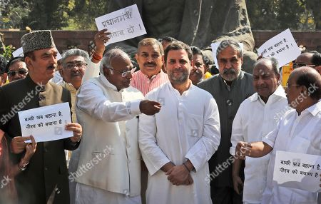 """Indian Congress party lawmakers shout slogans as their party president Rahul Gandhi, center, watches during a protest outside Indian parliament house in New Delhi, India, . The protest was against the ruling Bharatiya Janata Party and billionaire jeweler Nirav Modi, who is being alleged $1.8 billion bank fraud reported using fake bank documents to obtain overseas loans. Banners in local language read: """"All other things are excuses, basically you have to save Nirav, Answer please prime minister"""