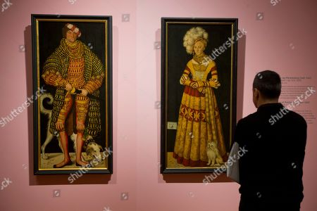 A man looks at two portraits by Lucas Cranach the Elder, Henry the Pious, Duke of Saxony, left, and Catherine of Mecklenburg, right, part of the High Society exhibit at the Rijksmuseum in Amsterdam, Netherlands, . High Society includes life-size, standing full-length masterpieces by some great painters like Rembrandt, Velasquez, Frans Hals, Reynolds, Manet, Sargent, Van Dyck, Gainsborough, Lucas Granach the Elder, and Munch among others