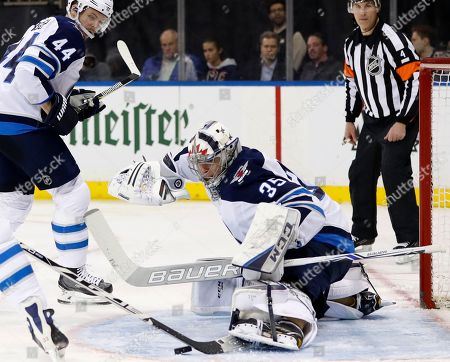 Steve Mason, Josh Morrisey. Winnipeg Jets goaltender Steve Mason (35)makes a save with his skate as Winnipeg Jets defenseman Josh Morrissey (44) watches over his shoulder during the second period of an NHL hockey game in New York