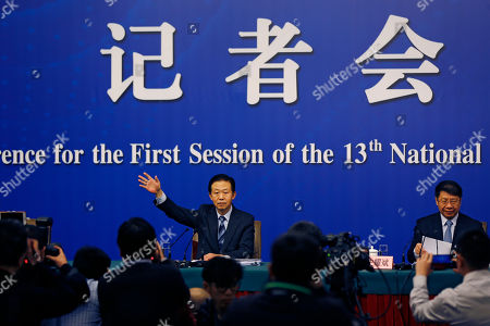 Stock Picture of China's Finance Minister Xiao Jie waves as he arrives for a press conference on the sidelines of the National People's Congress at the media center in Beijing, . Xiao tried Wednesday to defuse concern over the country's rising debt, saying government borrowing is below danger levels and regulators can prevent financial system risks