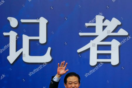 China's Finance Minister Xiao Jie waves as he arrives for a press conference on the sidelines of the National People's Congress at the media center in Beijing, . Xiao tried Wednesday to defuse concern over the country's rising debt, saying government borrowing is below danger levels and regulators can prevent financial system risks